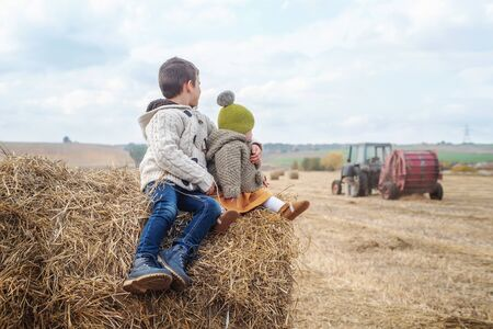 a yang boy and a little girl near a haystack in a field at sun day on autumn next to a tractor cleans field Zdjęcie Seryjne