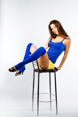 Full-length portrait of a woman with perfect slim beautiful body on chair Stock Photo - 17237414