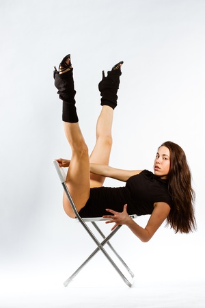 Full-length portrait of a woman with perfect slim beautiful body on chair photo
