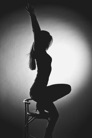 Erotic silhouette of a beautiful young woman sitting on a chair photo
