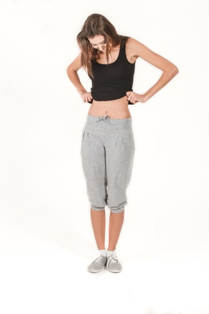 cintura perfecta: Chica joven con una figura delgada agraciada aislada en el fondo blanco que mira en el peor est�mago y cintura perfecta