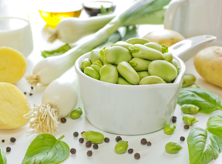 fava: Ceramic dipper of fava beans with ingredients for cream soup Stock Photo