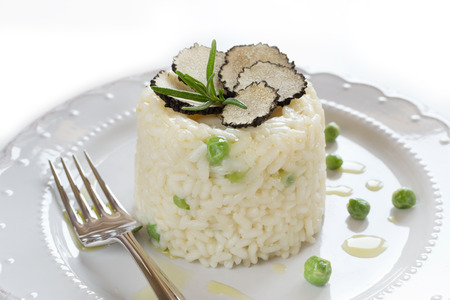 Italian risotto with black truffle and green peas on white plate Stok Fotoğraf