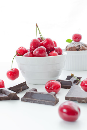 Cherries in white bowl with chocolate and cupcake on white background photo