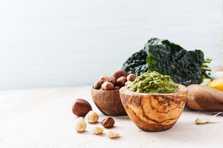 cooking oil: Veggie recipe - homemade pesto with kale and hazelnuts in wooden bowl on marble table with free text space. Healthy concept.
