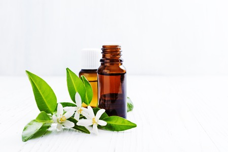 Neroli (Citrus aurantium) essential oil in a brown glass bottle with fresh white  flowers on ligth background. Selective focus.