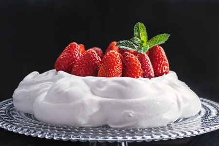 Pavlova - meringue cake with  fresh strawberries  on  glass cake stand on old vintage  black wood  background. Top view, copy space, close up, selective focus. Stock Photo