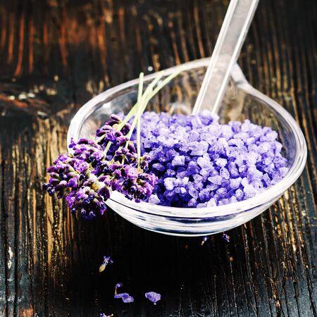 lavender coloured: ingredients for lavender spa on black wooden background.
