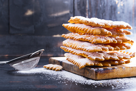 crostoli: Italian Frappe or chiacchiere  - typical Italian carnival fritters dusted with powdered sugar on   old black wooden table. With free text space.