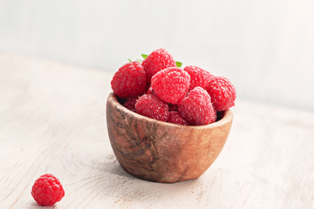 Fresh raspberries in  olive wooden bowl  on  old  wooden board, with copy space. Selective focus.