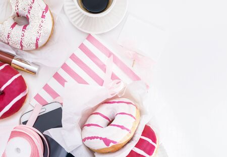 stil: Donuts, mobile phone, gift  on white  table, top view with copy space. Flat lay image. Stock Photo