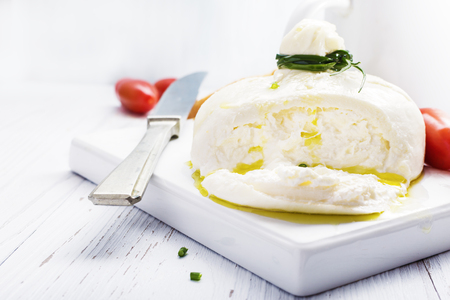 Italian burrata cheese with basil onion olive oil on white   plate on light background. Selective focus, free text space. Foto de archivo