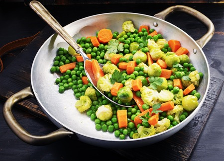 brussels sprouts with green peas cavoulflower in a pan on a old black board. Stock Photo