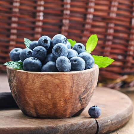 Blueberry in wooden bowl on rustic background. Stock Photo