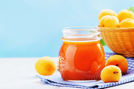 Apricot jam in a glass with apricots on a light background. Copy space.