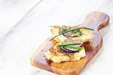 Italian black truffle bruschetta with herbs and oil on grilled or toasted crusty ciabatta bread Archivio Fotografico