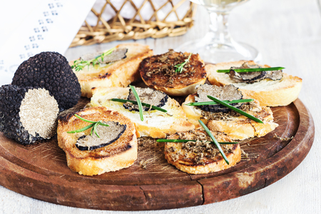 Italian black truffle bruschetta with herbs and oil on grilled or toasted crusty ciabatta bread Stock Photo