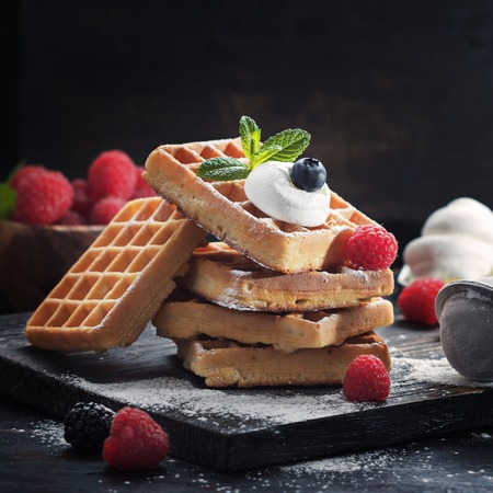 Waffles with summer raspberries served on black old rustic background.