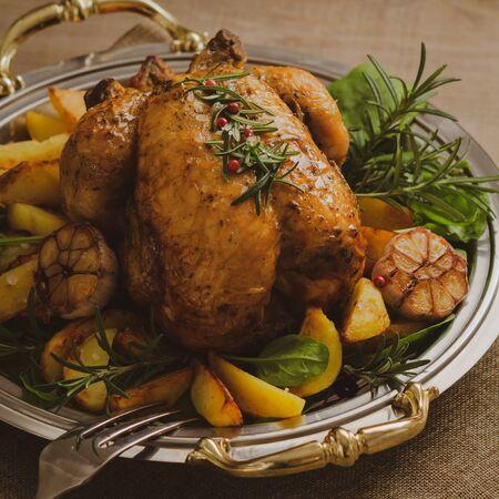 Poulet et pommes de terre rôtis, épinards, ail et romarin sur plaque de métal festive.