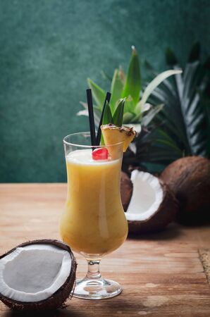 Tropical caribbean cocktail Pina Colada in a glasses on wooden  table with coconut and pineapple. Stock Photo