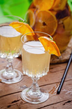 Glass jug of white sparkling wine sangria decorated with citrus slices and season fruits on wooden table. Stock fotó
