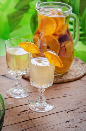 Glass jug of white sparkling wine sangria decorated with citrus slices and season fruits on wooden table. Stock fotó - 130162952