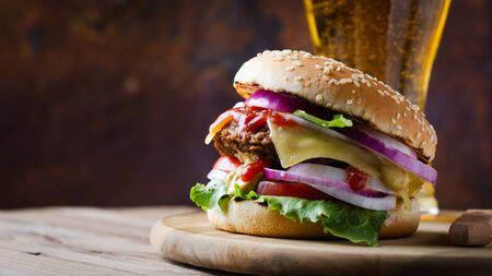 Traditional burgers with cutlet, fresh vegetables, crispy bun with sesame seeds with glass beer on a wooden  table.