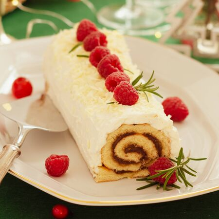 White chocolate cream yule log Christmas cake with  raspberries.