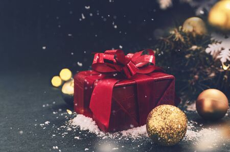 Red gift box with snow in Christmas decor on the dark blue
