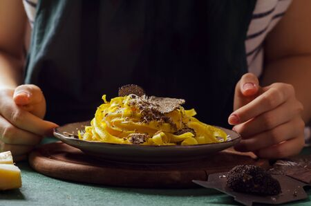 Female hands grating Parmesan cheese, black truffle onto pasta tagliatelle. Stok Fotoğraf