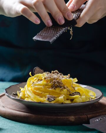 Female hands grating parmesan cheese, black truffle onto pasta tagliatelle.