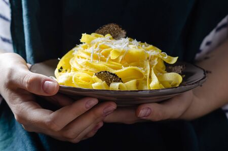 Female hands holding plate with pasta tagliatelle with parmesan cheese and black truffle.