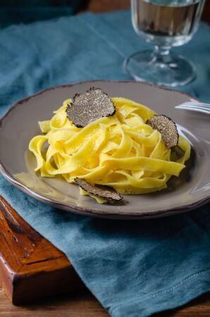 Italian cuisine- tagliatelle with black truffle on rustic plate. Stok Fotoğraf