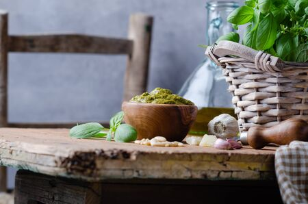 Pesto sauce in a olive wooden bowl with pine nuts, basil, parmesan and garlic over rustic table.