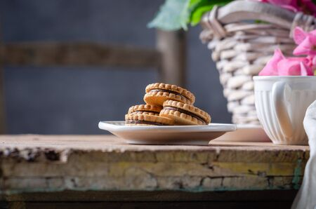 Still-life in the rustic style with cookies and hortensia flower in basket on wooden table. Stok Fotoğraf