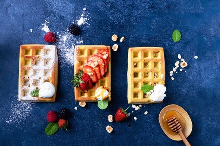 Belgian waffles with  summer fresh berries and honey on blue stone Banco de Imagens