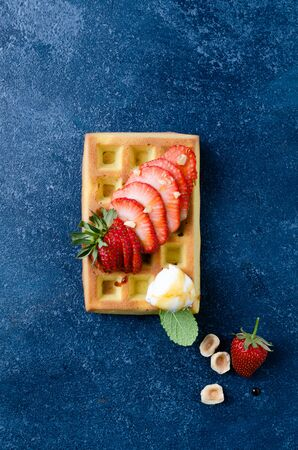 Belgian waffles with  summer fresh berries and honey on blue stone, Top view. Banco de Imagens - 130163715