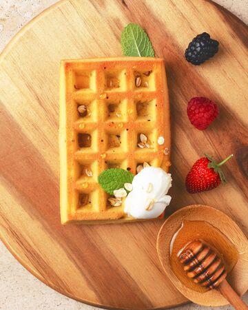 Belgian waffles with  summer fresh berries and honey on wooden board.Top view. Banco de Imagens - 130163716