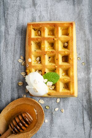 Belgian waffles with  oat flakes and honey on grey wooden board. Banco de Imagens - 130163718