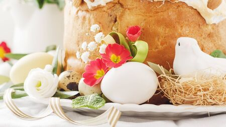 Italian Easter  cake with flowers eggs, dove on white plate. Selective focus, free text space. Banco de Imagens - 130163727
