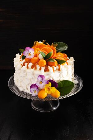 Festive cake with citrus fruits and flowers with streaks of caramel on  black