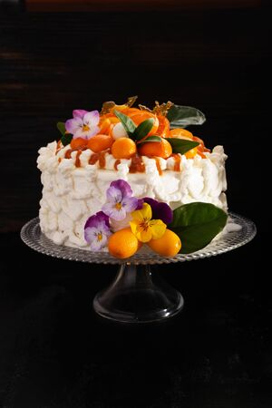 Festive cake with citrus fruits and flowers with streaks of caramel on  black 版權商用圖片 - 130163001