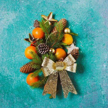 Christmas composition with tangerines, branches of spruce and pine cone on green blue