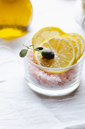 Ingredients for body scrub of pink salt with lemon and olive oil, eco bio friendly cosmetic for skin care.