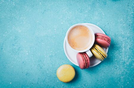 Cup of coffee and  macarons.  Colorful turquoise background.