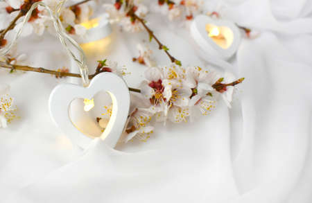 Close up romantic composition with blooming almond branch, couple of heart lights on white silk background. Elegant greeting concept for Valentines day, Mothers day, Womans day or wedding. Banco de Imagens