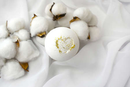 Luxury spa composition. White bath bomb with cotton flowers on silk fabric background. Minimalist beauty concept. Romantic design for wedding, blogging or handmade cosmetic branding