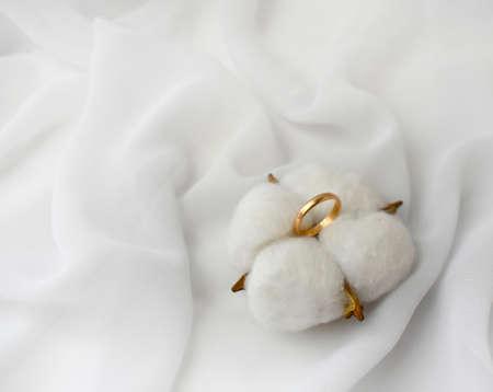 Elegant wedding concept. Golden ring with cotton flower pillow on white silk background. Feminine still life composition. Minimalist style. Copyspace.