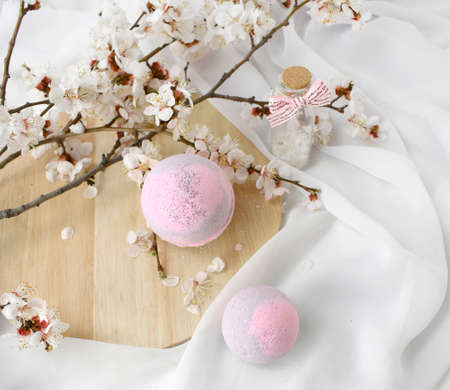 Elegant spa concept with pink bath bombs, sea salt and blossom branch on silk background. Luxury organic cosmetic. Greeting card for Mothers day, Valentines day or wedding. Banco de Imagens
