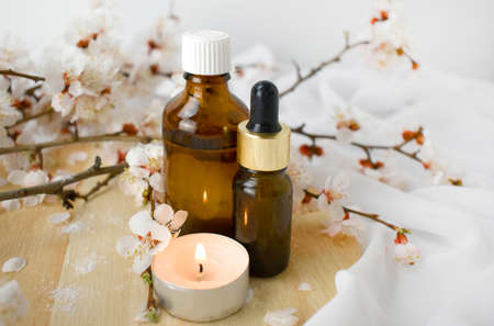 Aromatherapy concept with essential oil bottles, burning candle and blossom branch. Spa or herbal medicine still life composition. Copyspace.